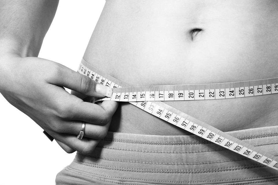 Jeune femme qui mesure son tour de taille suite à une séance de cryolipolyse