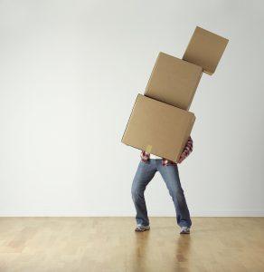 personne portant 3 cartons de déménagement