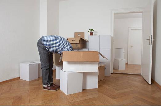 personne penchée la tête dans les cartons de déménagement