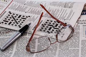 lunettes et journal avec grilles de mots croisés