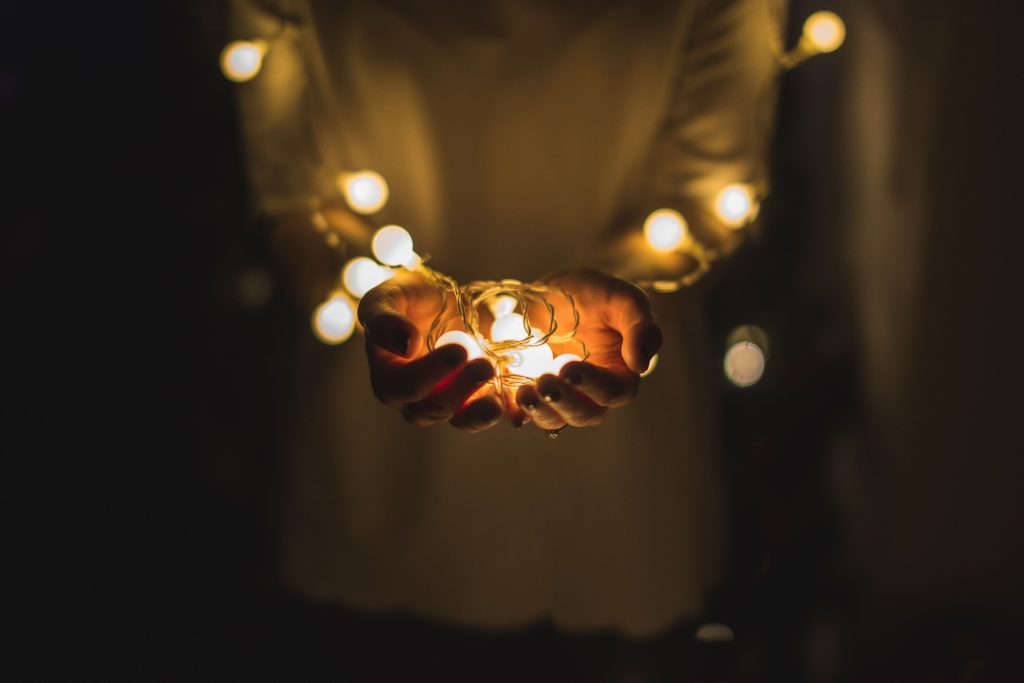 Mains tenant une guirlande lumineuse